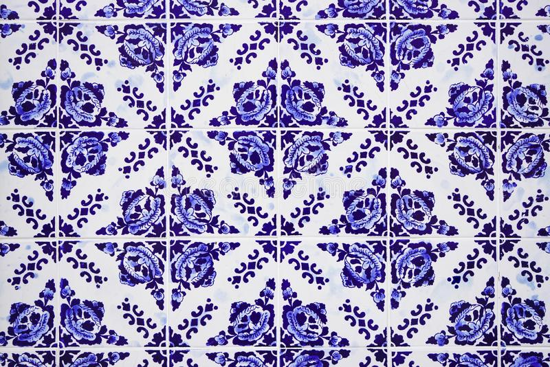 Gorgeous traditional Portuguese ceramic blue tiles with floral pattern. Vintage glazed tiles texture and background. stock photography