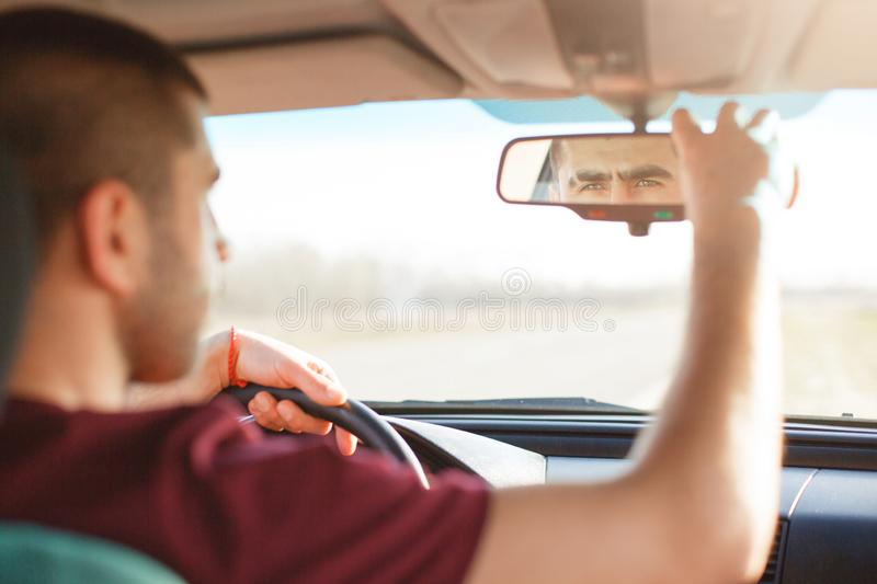 Horizontal photo of handsome dark haired unshaved male, regulates rear view mirror. Attractive man drives black car, looks traffic stock images