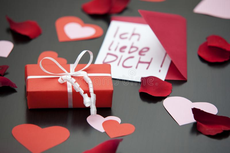 Love letter saying I love you in German and a red wrapped parcel. stock images