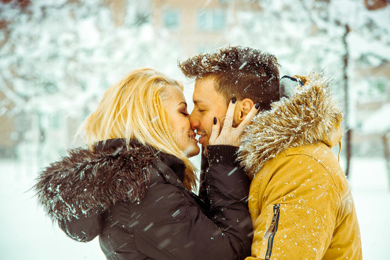 Horizontal photo of Man and woman happily kissing on the street. Horizontal photo of Man and women happily kissing on the street in the snow. Color high contrast stock photography
