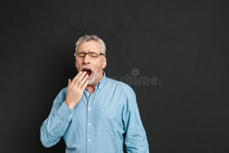 Horizontal photo of mature unshaved man 60s with grey hair wearing eyeglasses being sleepy and yawning because royalty free stock photography