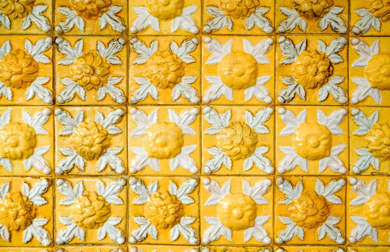 Old and dirty bright yellow relief tiles with floral pattern. Vintage glazed ceramic tiles texture and background. stock images