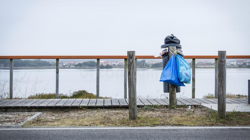Overflowing trashcan by the water and next to wooden footbridge. Prevention against Plastic in the Ocean epidemic. royalty free stock photos