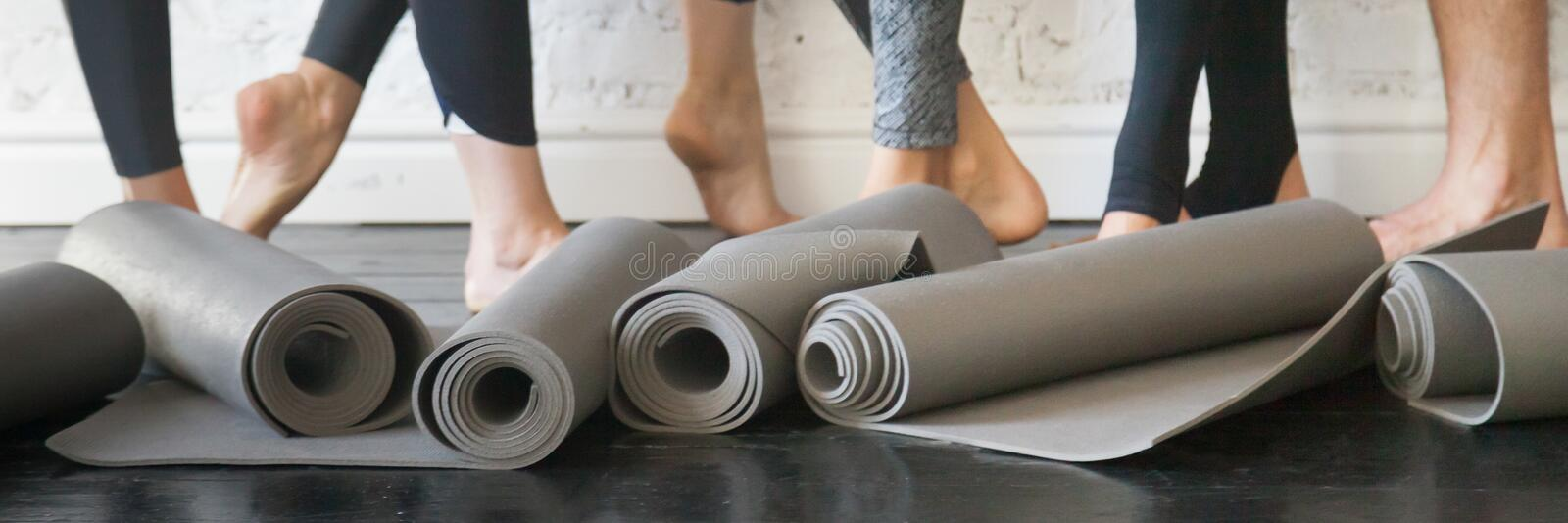 Horizontal photo people legs and rubber mats in roll closeup. Horizontal photo people standing after work out, close up yoga mats grey carpets in roll and stock images