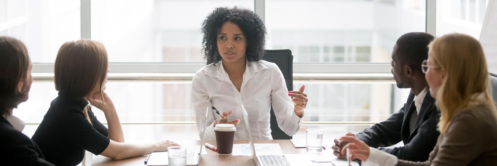 Horizontal photo african female boss talking at corporate meeting. Horizontal photo people sitting at boardroom african business women talking with staff at royalty free stock photography