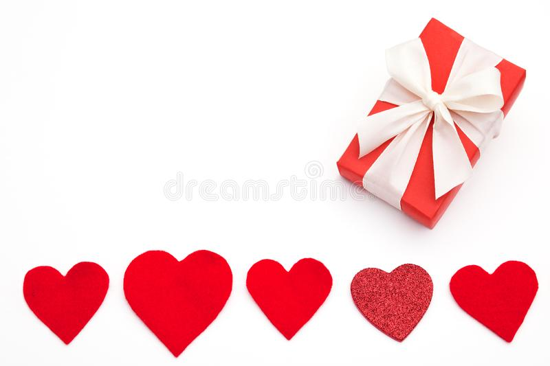 Present for Valentine`s day, Mother`s day or Wedding, wrapped in red paper, white bow and red hearts. stock images