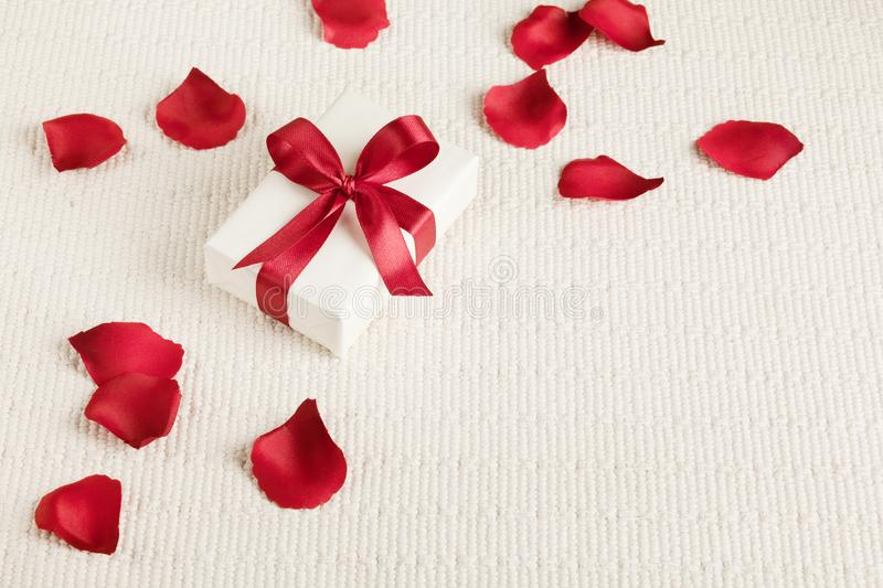 Present for Valentine`s day, Mother`s day or Wedding, wrapped in white paper, red bow and surrounded by red rose petals. royalty free stock photos