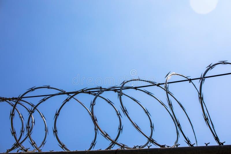 Horizontal photo of razor wire fence stock photo