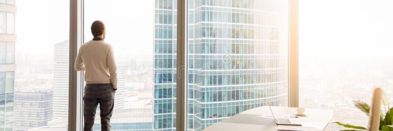 Horizontal image rear view businessman standing looking through panoramic window royalty free stock image