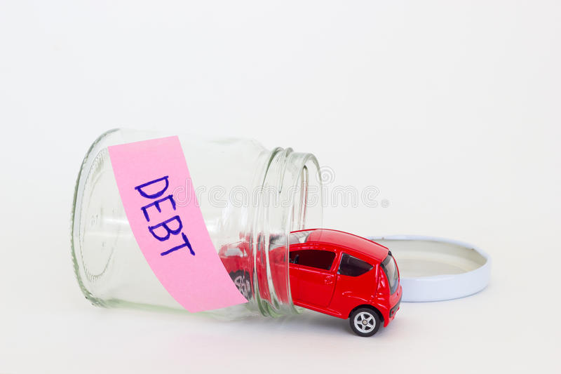 Horizontal photo of red car toy going into the glass bottle with. The word DEBT on its pink label stock photography