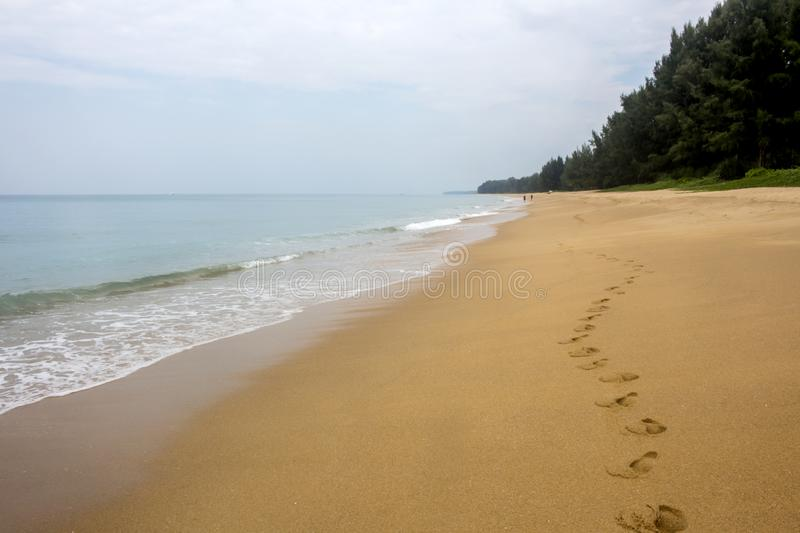 Seascape with row of footprints in golden sand at an almost deserted Mai Khao beach in Phuket, Thailand royalty free stock photos