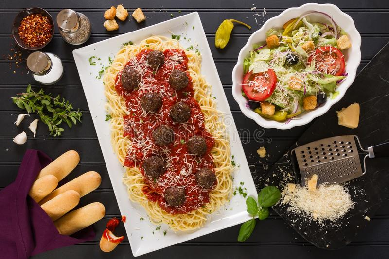 Spaghetti Dinner with Parmesan Cheese, Meatballs, Breadsticks and Salad. Horizontal photo of a Spaghetti Dinner with Meatballs, Breadsticks, Salad, Parmesan stock image