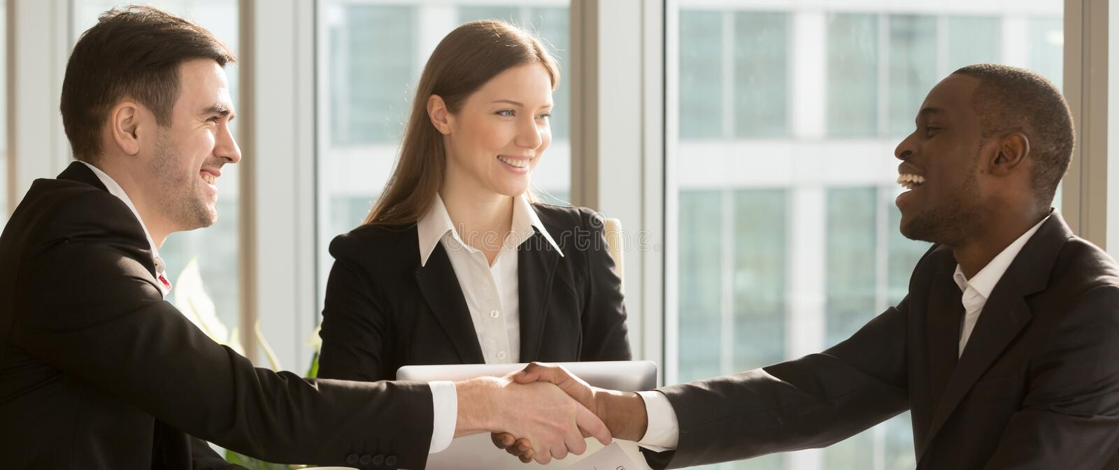 Horizontal image black and caucasian businesspeople greeting each other handshaking stock images