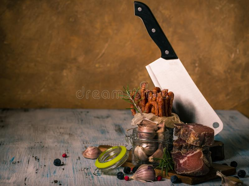 Dried italian meat from wild boar on chopping board with small sausages and garlic stock photo