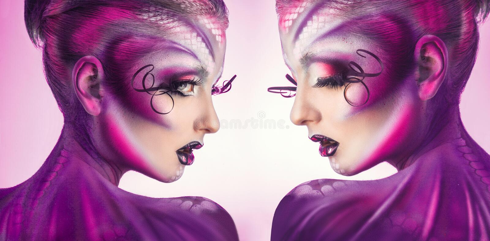 Horizontal photo of two women with creative magenta body art. Horizontal photo of two woman with creative magenta body art in studio royalty free stock photography