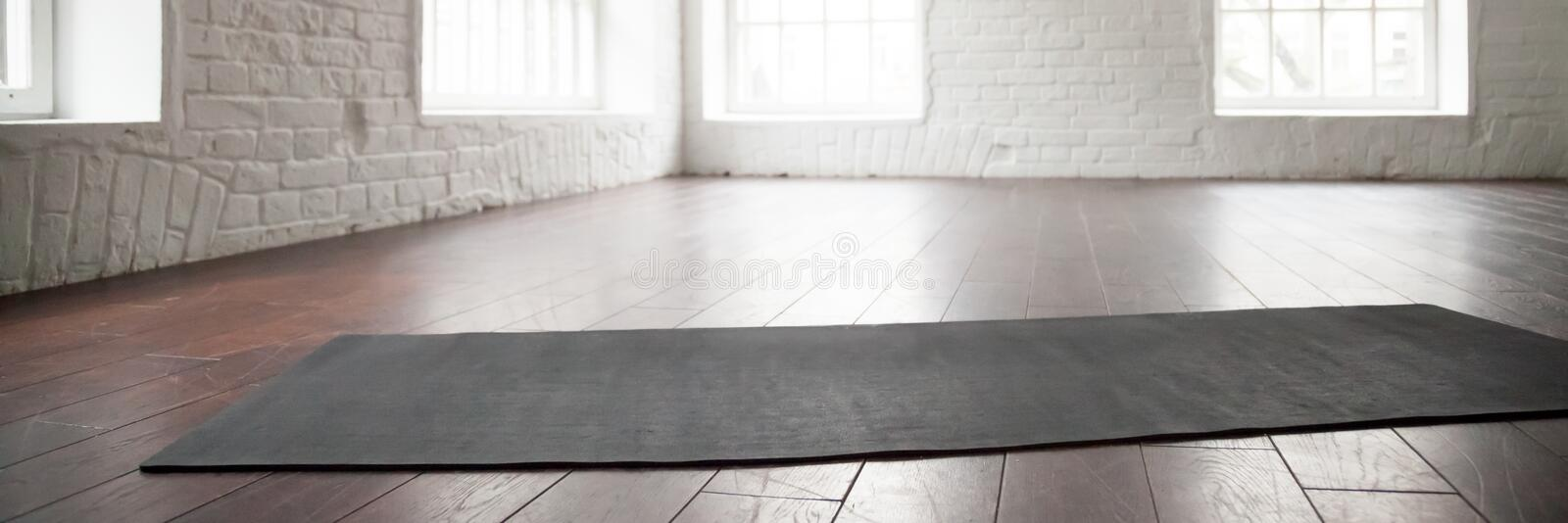 Horizontal photo yoga mat on wooden floor at sport club. Horizontal image personal yoga pilates rubber mat carpet on wooden floor at modern room of sport center royalty free stock image