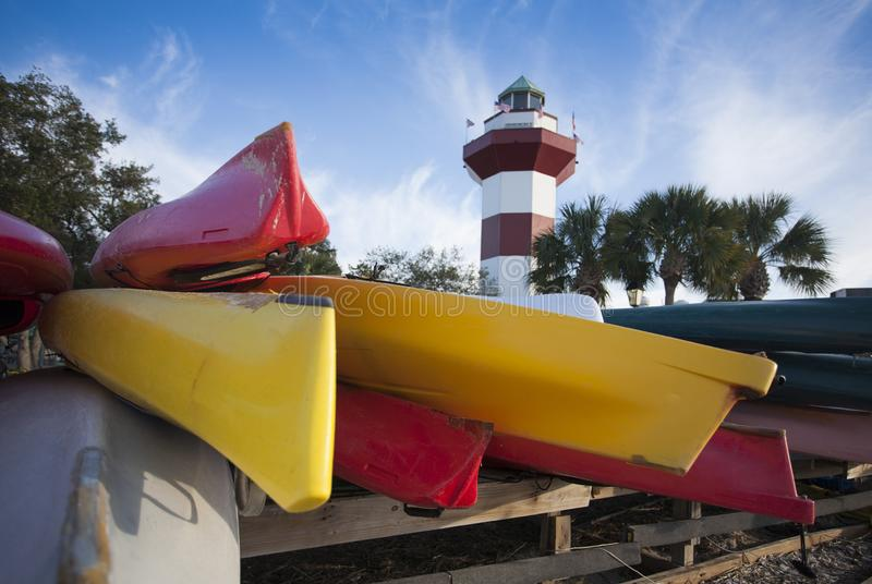 Colorful Kayaks in front of a Red and White Lighthouse stock photos
