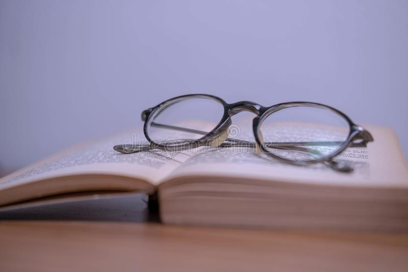 Horizontal photography in vintage style glasses and an old yellowed book. On a wooden table stock photo