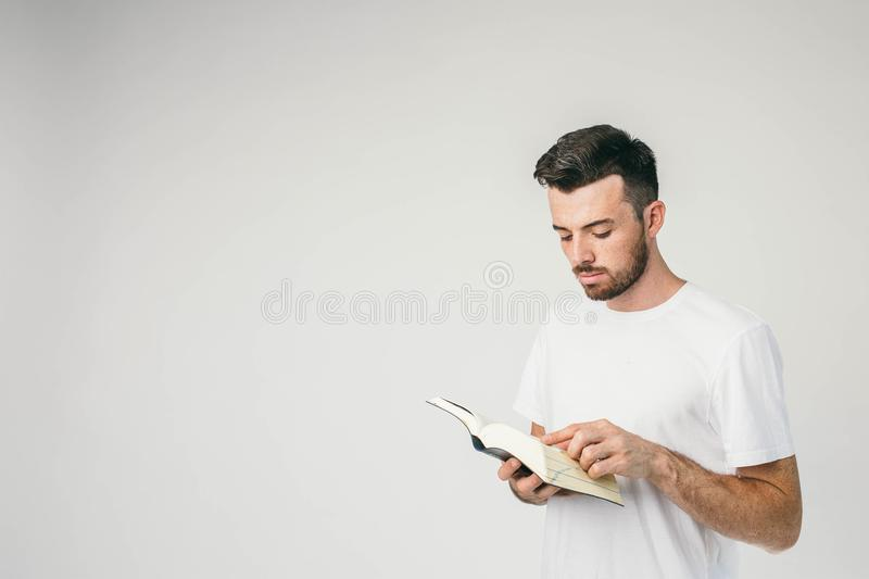 Horizontal photot of a young man standing near the white wal and reading a book. It is so interesting he cannot turn his stock image