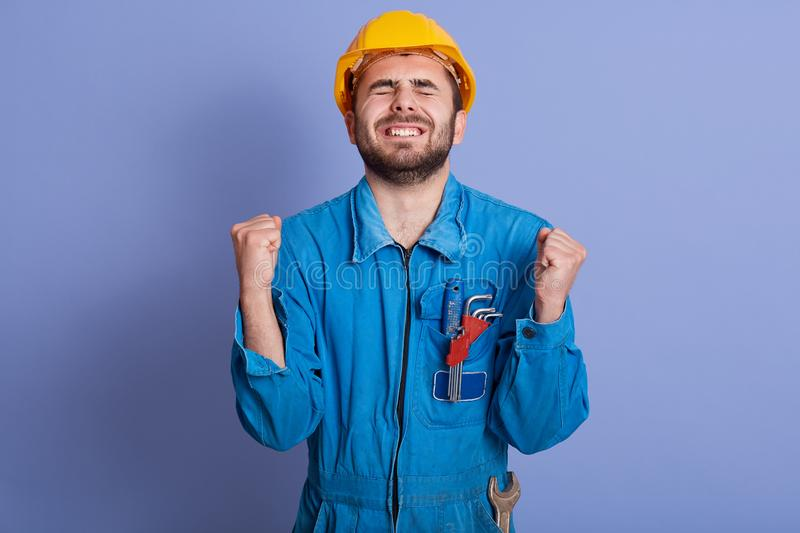 Horizontal picture of exhausted construction worker clenching his fists, raising hands, closing eyes, being tired of work, wearing royalty free stock images