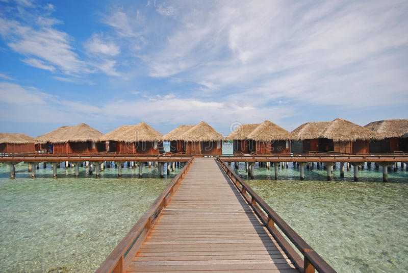 Horizontal picturesque View of Wooden Bridge Walkway leading to a Row of Luxury Overwater Villa royalty free stock photos