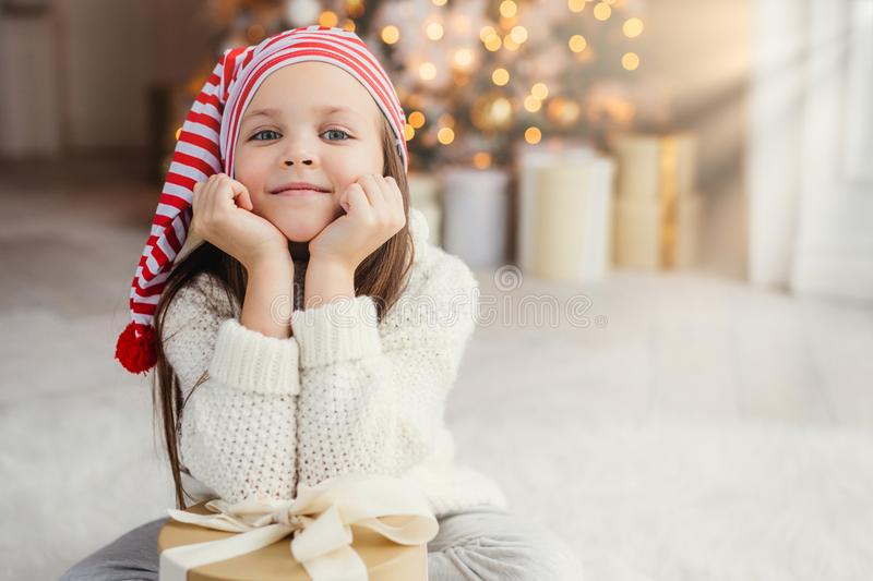 Horizontal portrait of adorable little child, leans on hands with present box, sits against decorated Christmas tree. Blue eyed sm. All kid in knitted white stock photos