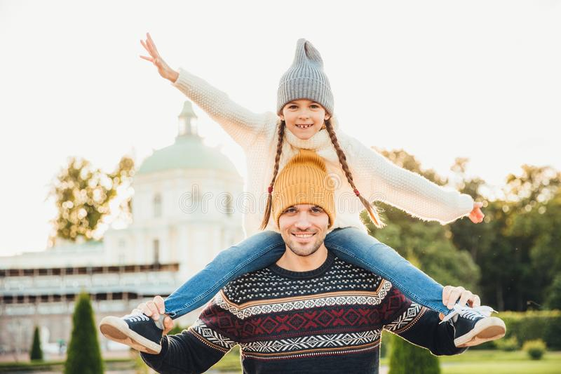 Horizontal portrait of affectionate father gives piggy back ride to his daughter outside, play together, have fun. Happy little ch royalty free stock photos