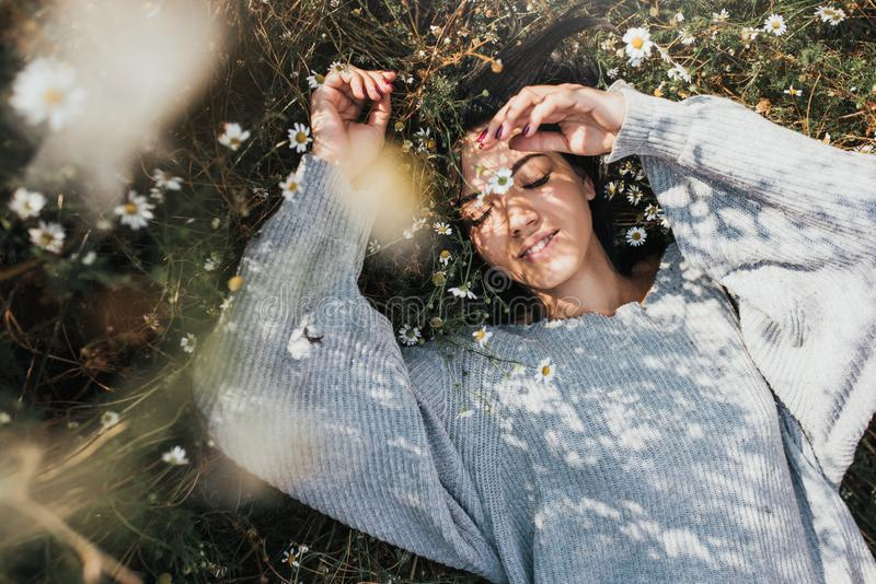 Horizontal portrait of an attractive Caucasian woman smile and feel free and dream on meadow with copy space. Beautiful brunette stock photo