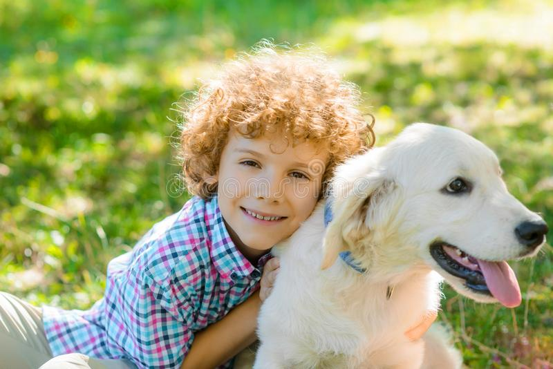 Horizontal portrait of a boy. With his favorite pet with his tongue out. Little child embraces his dog with sincere smile royalty free stock photo