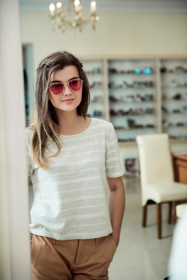 Horizontal portrait of charming young european female customer standing in optician store, trying stylish pair of stock image