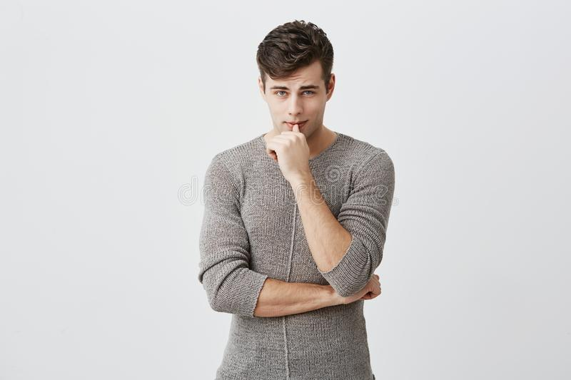 Horizontal portrait of confident serious attractive caucasian man keeping hand under chin, touching lips, wearing casual royalty free stock photos