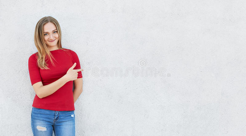 Horizontal portrait of cute woman wearing red sweater and jeans standing near white concrete wall poiting with her index finger at. Copy space for your stock photo