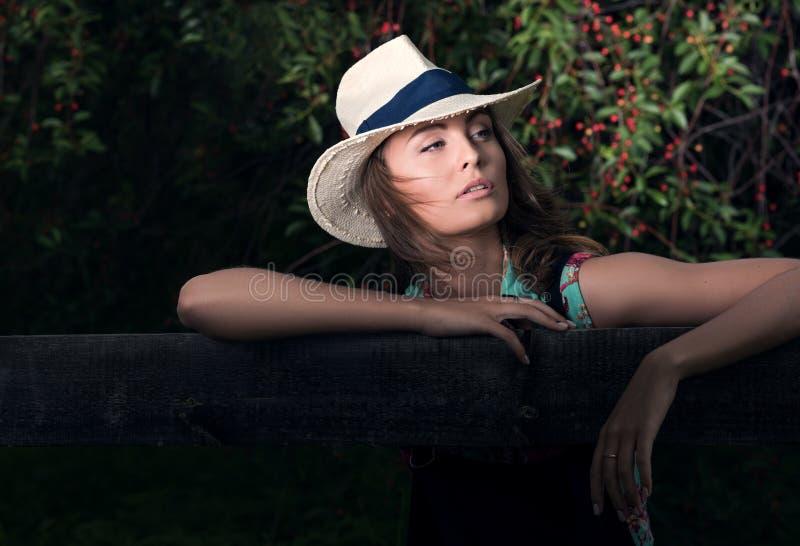 Horizontal portrait in dark tones outdoors. Young attractive woman, cherry. Horizontal portrait in dark tones outdoors. Young attractive woman in the background royalty free stock photo