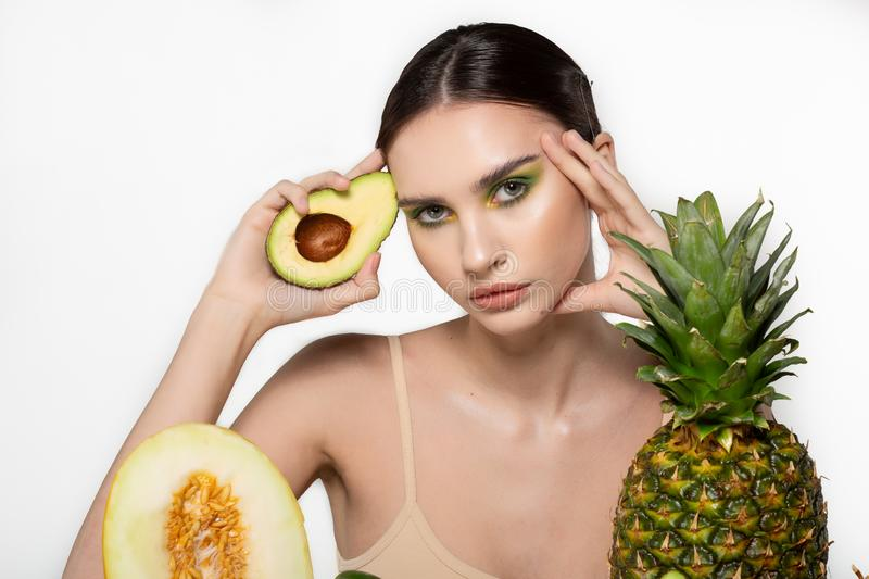 Horizontal portrait of european woman with half of avocado in hand, melon and pineapple in front, isolated against grey stock photography