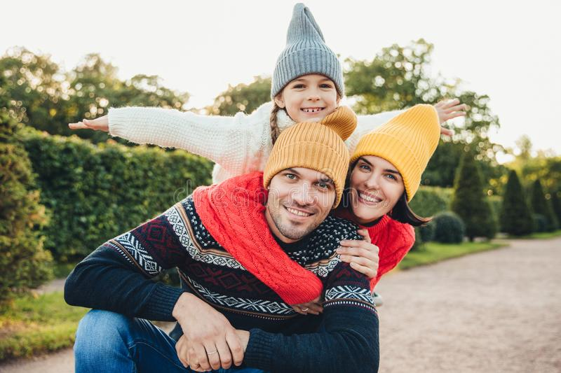 Horizontal portrait of family members spend free time together, embrace, encourage each other, have fun. Little smiling girl feels royalty free stock photography