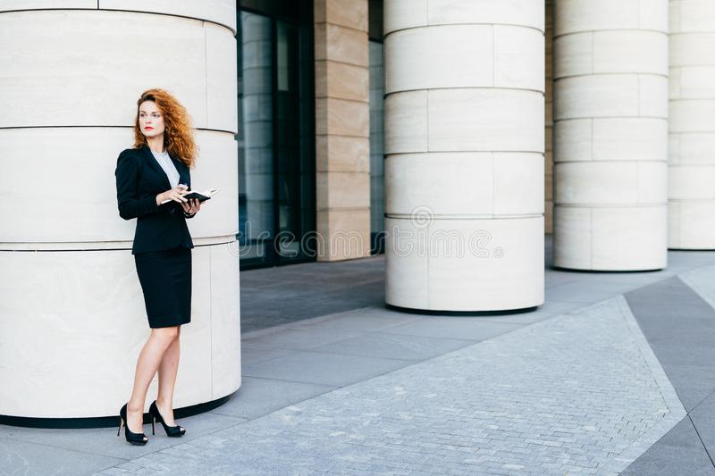Horizontal portrait of good-looking businesswoman dressed in formal clothes and black shoes with high heels, holding pocket book, royalty free stock image