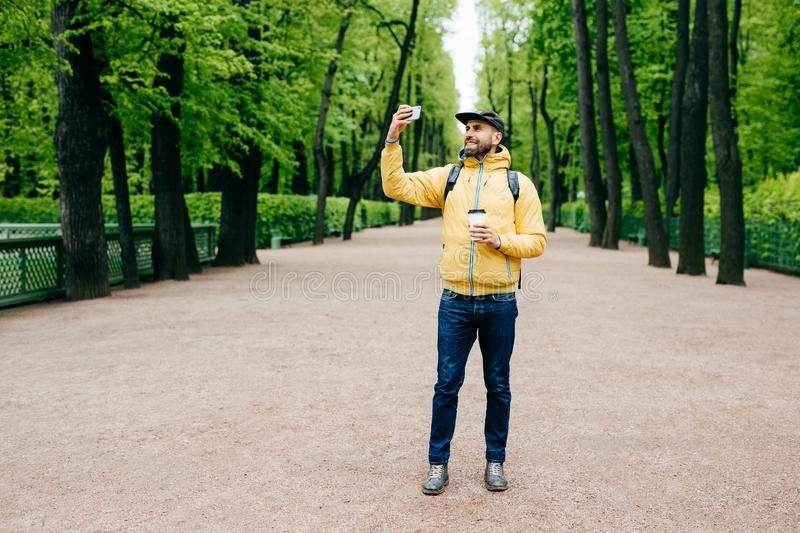 Horizontal portrait of handsome bearded man in yellow anorak, cap and jeans having happy expression while posing in park making se stock photo