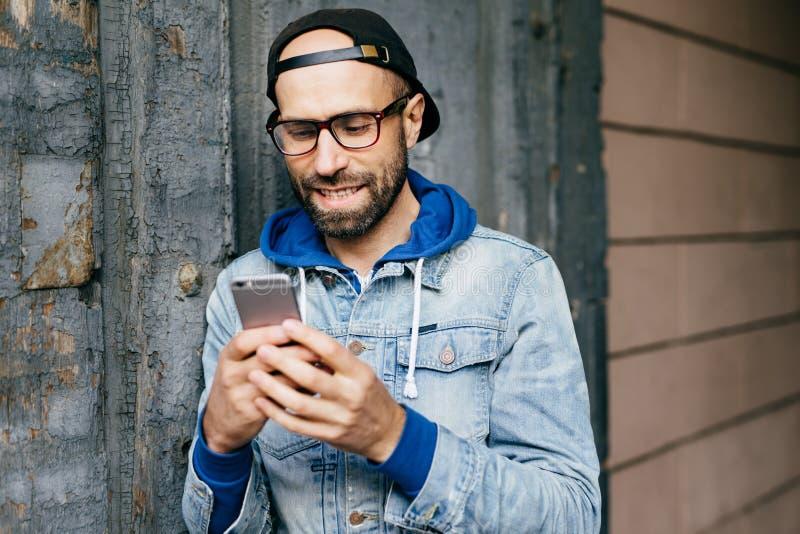 Horizontal portrait of handsome bearded stylish man in denim anorak wearing big eyeglasses holding smartphone using free Internet, royalty free stock photography