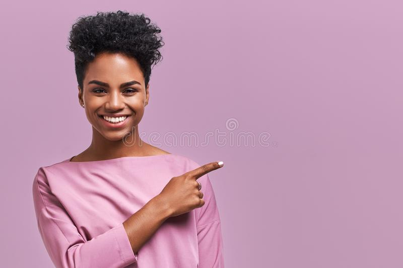 Horizontal portrait of happy dark skinned mixed race female model indicates with fore finger at blank copy space, shows royalty free stock images