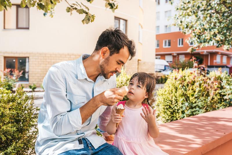 Horizontal portrait of little girl sitting with dad on the street and eating ice-cream outdoor. Happy kid wears dress spending. Time together with father. Good stock image