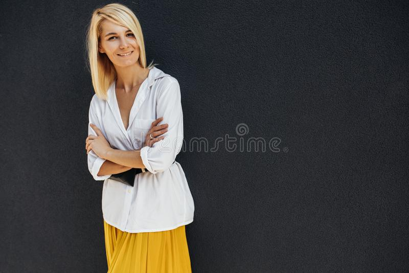 Horizontal portrait of pretty smiling beautiful young blonde female standing with her arms crossed and looking at camera against stock photography
