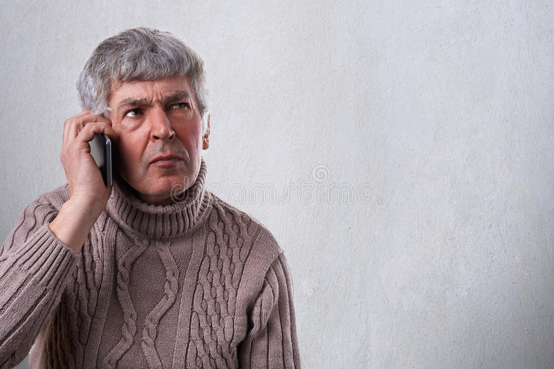 A horizontal portrait of serious, worried, upset mature man talkiing on cellphone. An old employee deciding some problems over tel stock photography