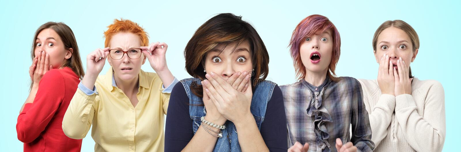 Horizontal portrait of several female closes hands over mouth in shock by what they heard. royalty free stock image