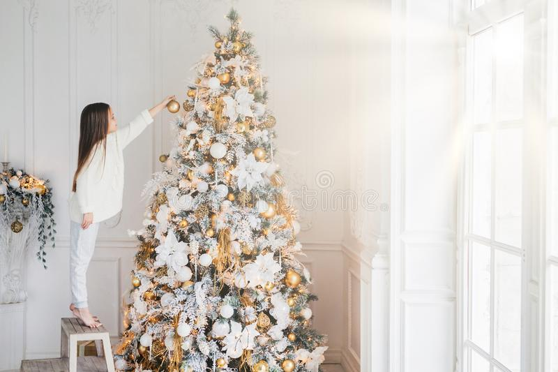 Horizontal portrait of small female child stands on chair, decorates Christmas tree, tries to show best, being at home, enjoys dom. Estic calm atmosphere, wants stock image