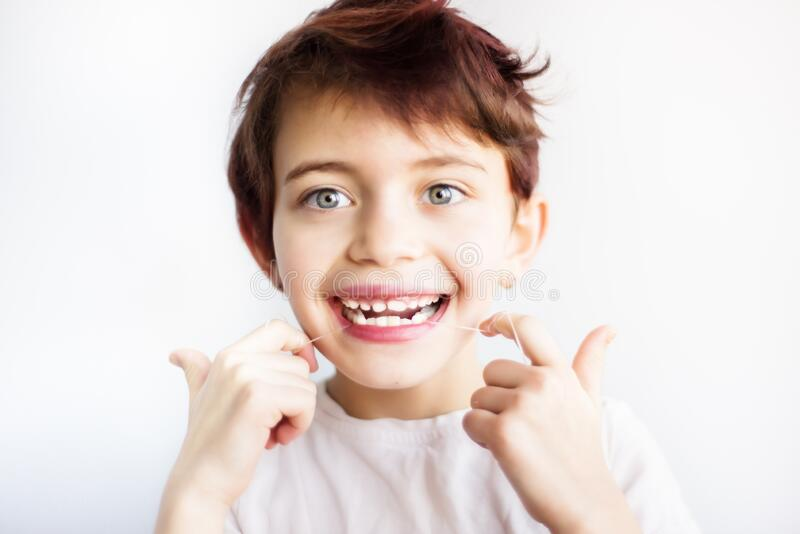 Horizontal portrait of 7 years old smiling child in white t-shirt flossing his teeth on white background isolated. Healthcare and. Dental care from childhood royalty free stock photos
