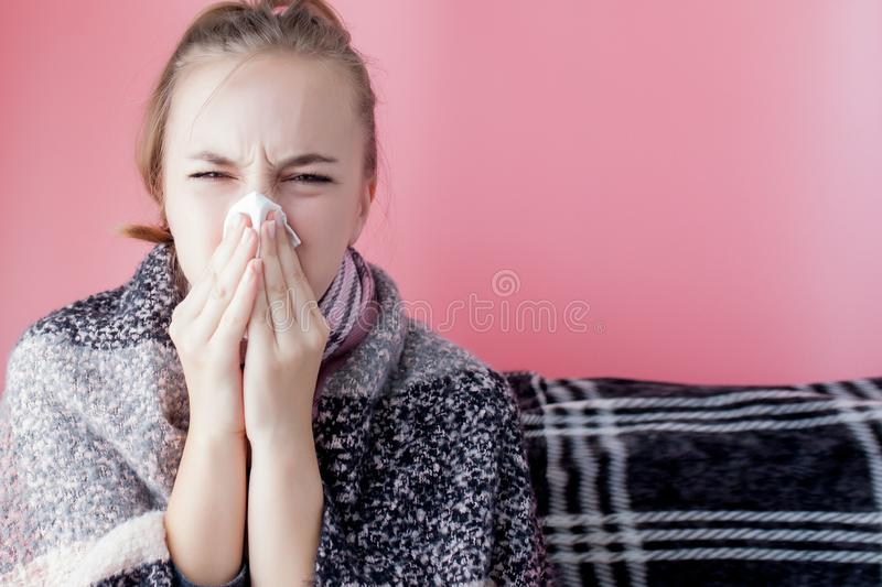 Horizontal portrait young girl with a handkerchief and runny nose in profile, sneezing from flu, white skinned female model at royalty free stock photography
