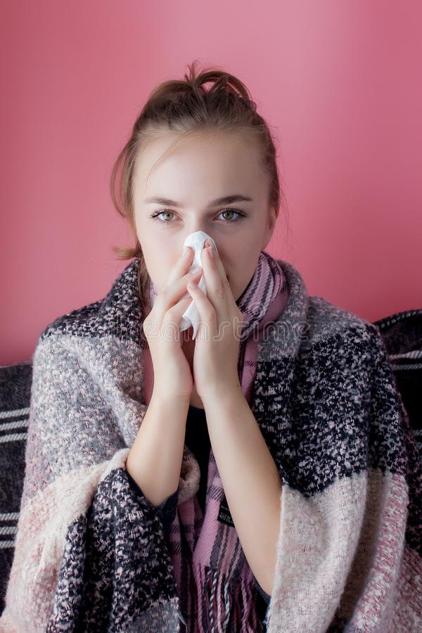 Horizontal portrait young girl with a handkerchief and runny nose in profile, sneezing from flu, white skinned female model at stock photography