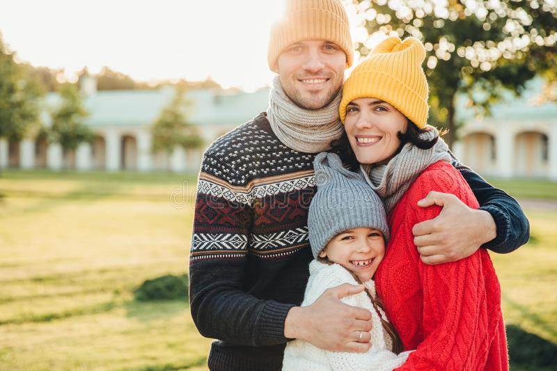 Horizontal portrait of young handsome man in yellow hat and warm knitted sweater, embrace his wife and daughter, pose at camera wh. Horizontal portrait of young royalty free stock images