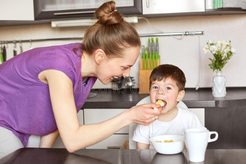 Horizontal portrait of young mother in casual outfit, feeds child with spoon, gives him healthy food, take care of son, pose at ki stock images