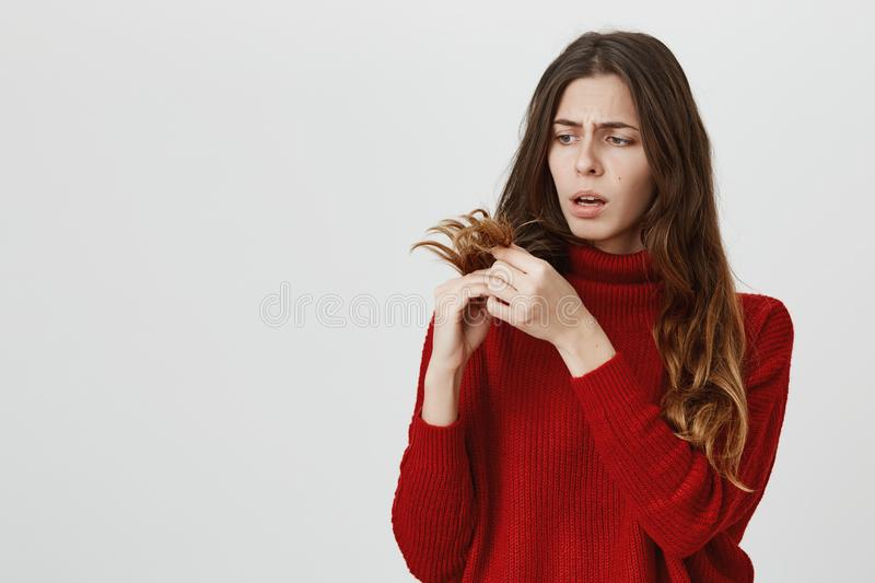 Horizontal portrait of young upset stunned woman in red sweater looking with sad expression of face at her dark long royalty free stock photography